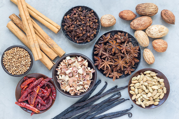 Aromatic winter spices in bowls and on background, top view, horizontal - Stock Photo - Images