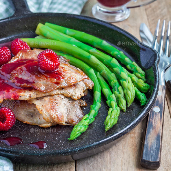 Pork cutlets with raspberry sauce and asparagus in iron cast pan, square - Stock Photo - Images