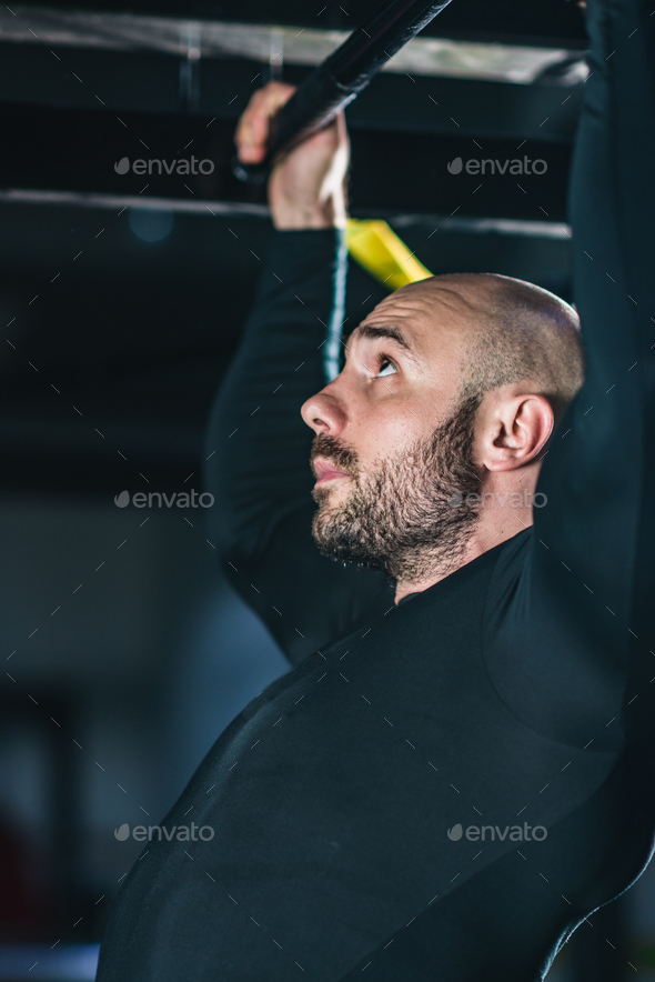 Man doing pull-ups in the gym - Stock Photo - Images