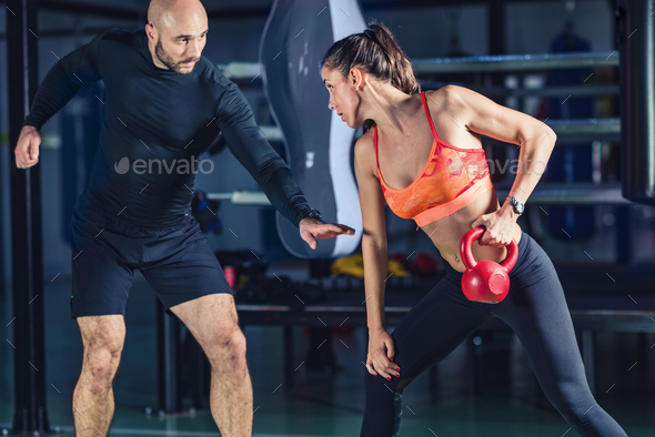 Personal trainer exercising with kettlebell with woman in the gy - Stock Photo - Images