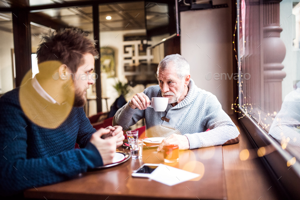 Senior father and his young son in a cafe. - Stock Photo - Images