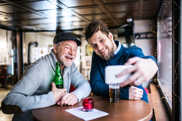 Senior father and his young son with smartphone in a pub. - Stock Photo - Images