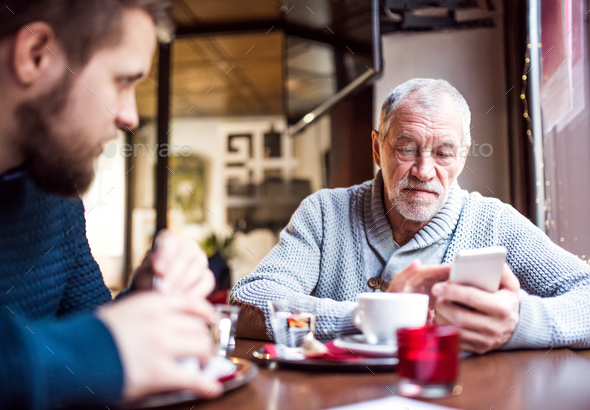 Senior father with smartphone and young son in a cafe. - Stock Photo - Images