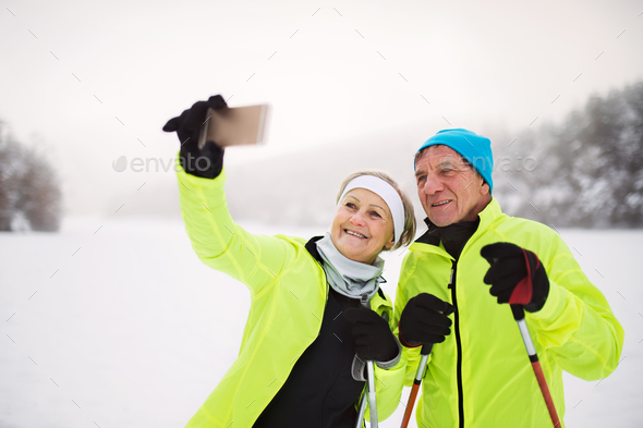 Senior couple with smartphone cross-country skiing. - Stock Photo - Images