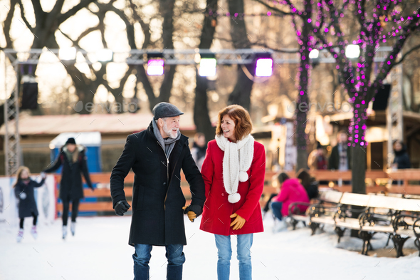 Senior couple on a walk in a city in winter. - Stock Photo - Images