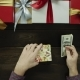Adult Man Puts Dollars Into Xmas Present Box on Wooden Decorated Table, Top Down Shot - VideoHive Item for Sale