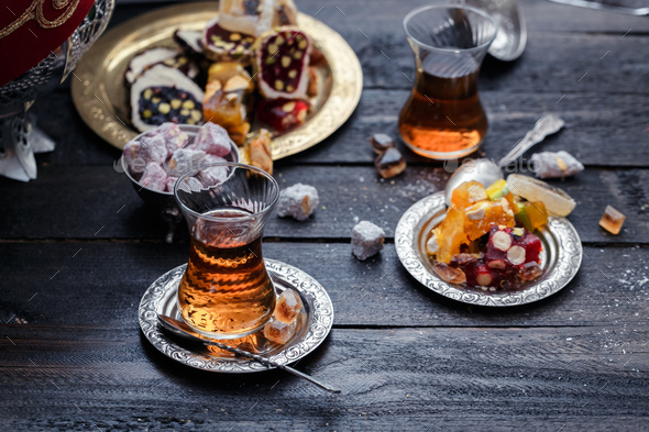 Cups of Turkish tea with oriental sweets on rustic wood - Stock Photo - Images
