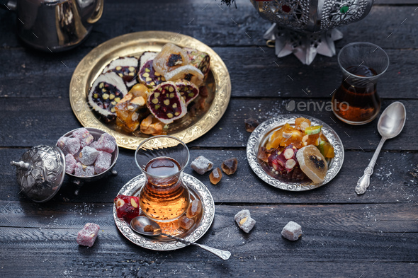 Cup of Turkish tea on saucer on rustic wood with snow in front of a dark blurred background - Stock Photo - Images