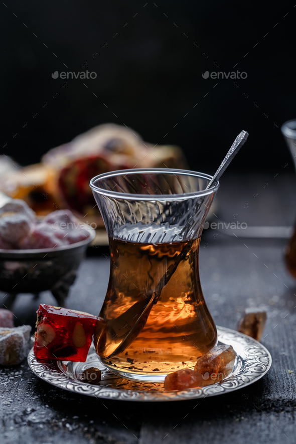 A glowing traditional glass of tea with blurred dark background - Stock Photo - Images