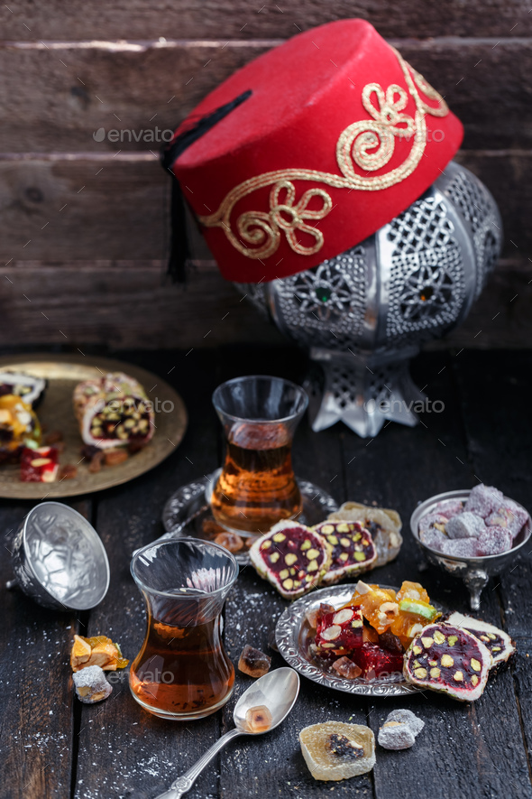 Turkish tea with authentic glass cups. Two cups of turkish tea and sweets on dark wood background - Stock Photo - Images