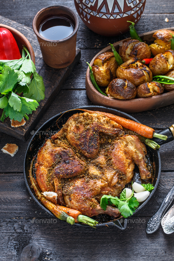 Whole roast chicken in an iron pan on dark background - Stock Photo - Images