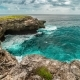 Wonderful Waves in Turquoise Ocean with the Cloudy Sky and Surrounding By the Cliffs in Nusa