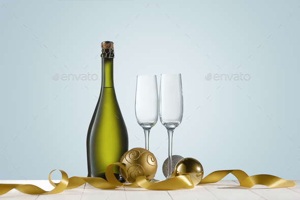 Glasses with champagne and bottle over sparkling holiday background - Stock Photo - Images