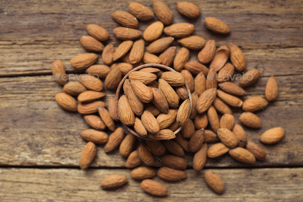 Almonds in brown bowl on wooden background - Stock Photo - Images