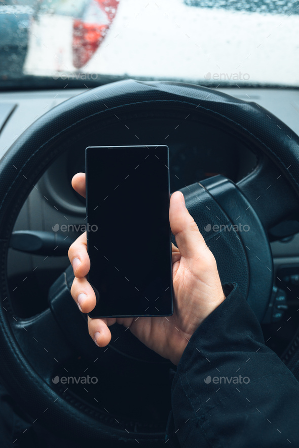 Man using smartphone in car - Stock Photo - Images
