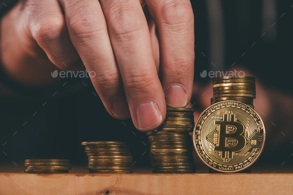 Bitcoin cryptocurrency miner stacking BTC coins - Stock Photo - Images