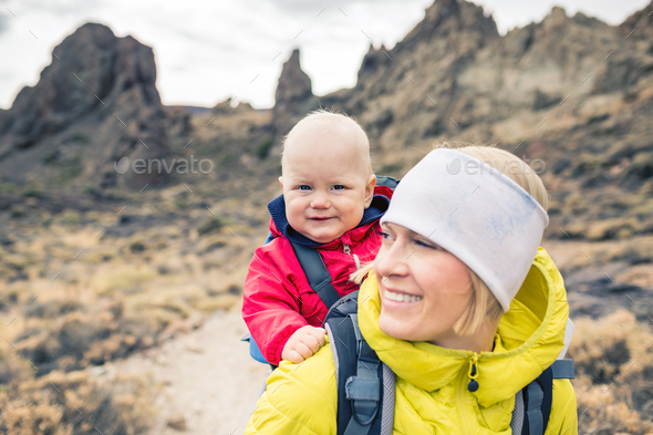 Happy mother with little boy travelling in backpack - Stock Photo - Images