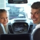 Funny Dad with His Daughter Sit in the Front Seats and Look at the Small Screen of the Car - VideoHive Item for Sale