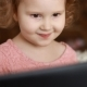 A Little Cute Girl Looks at the Screen Monitor Computer or Laptop. Funny Child Looking Tv, Video - VideoHive Item for Sale