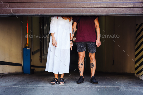 guy and girl behind the roller shutter - Stock Photo - Images