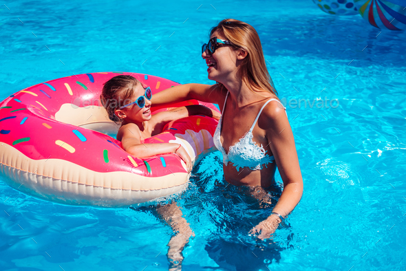 Little girl with her mom in swimming pool. - Stock Photo - Images