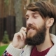 A Man With a Beard Speaks On the Phone - VideoHive Item for Sale