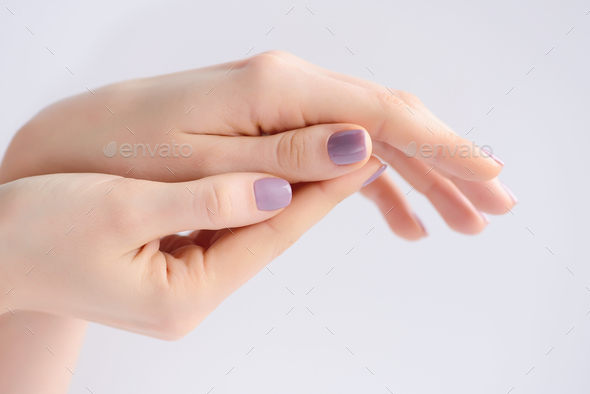Closeup of hands of a young woman with pink manicure on nails - Stock Photo - Images