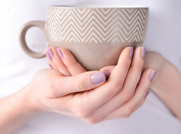 Hands of a young woman holding a cup of tea - Stock Photo - Images