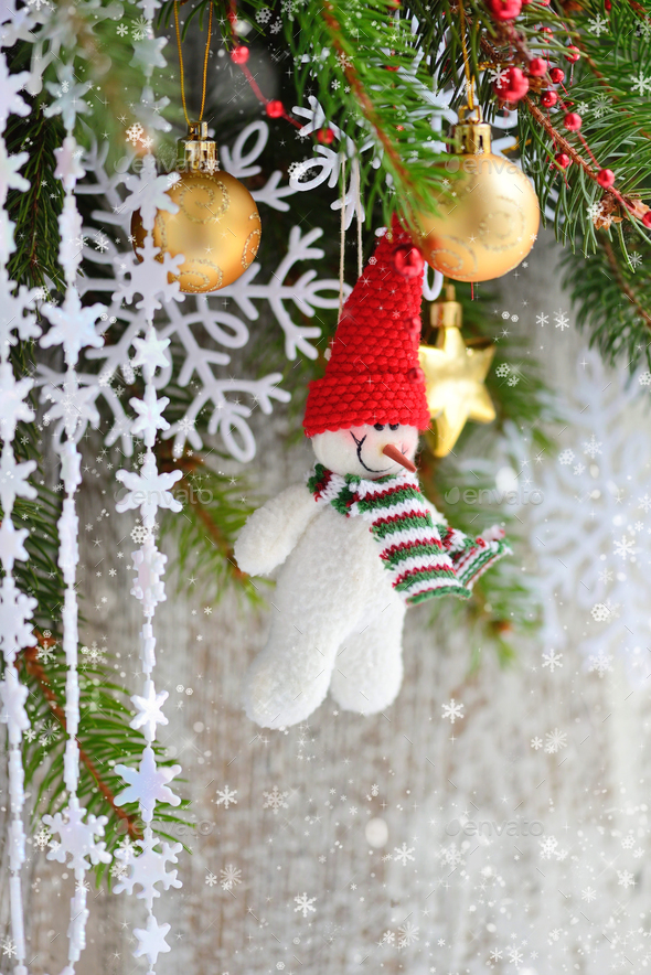 Snowman with Christmas ornaments on the branches of spruce - Stock Photo - Images