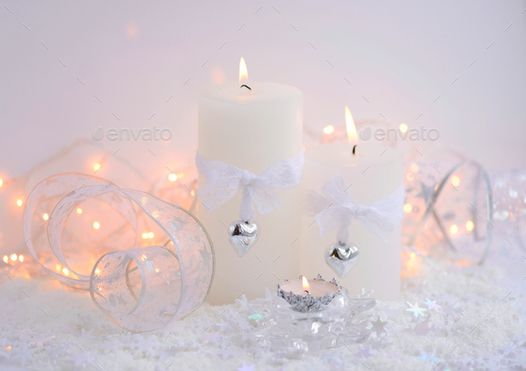 Christmas candles on the snow and Christmas lights. Festive Chri - Stock Photo - Images