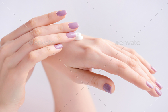 Women's hands with pink manicure applying cream. The concept of - Stock Photo - Images