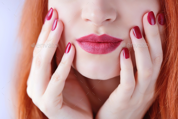 Beautiful red-haired young woman with red manicure, lipstick sam - Stock Photo - Images
