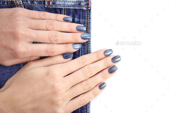 Female hands with dark blue manicured nails with jeans on white - Stock Photo - Images