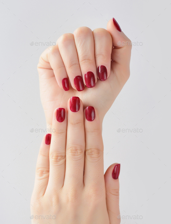 Closeup of hands of a young woman with red manicure on nails aga - Stock Photo - Images