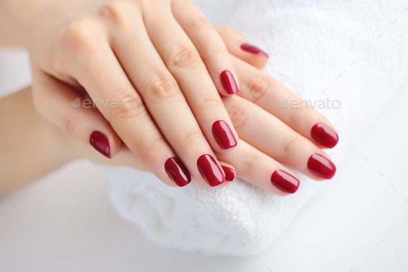 Hands of a woman with red manicure are on a towel - Stock Photo - Images