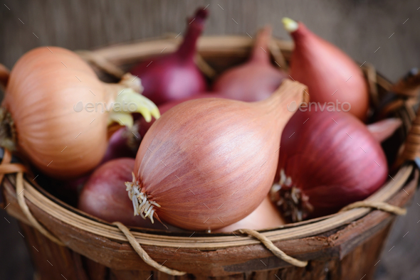 Dry bulb onions in a basket on wooden background - Stock Photo - Images