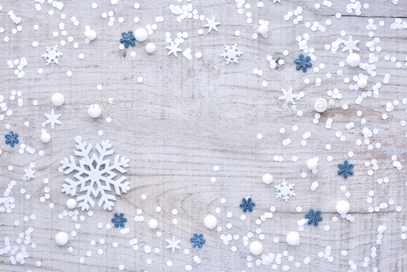 Snowflakes and confetti on a light wooden background. Festive Ch - Stock Photo - Images