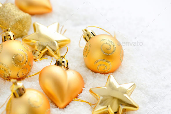 Christmas gold ornaments on the snow. Festive Christmas backgrou - Stock Photo - Images