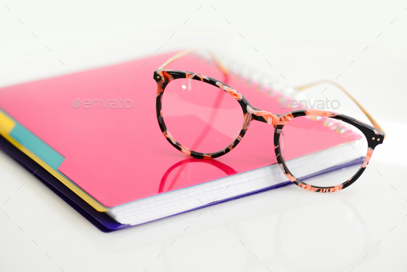 Eye glasses with pink spiral notebook on white background - Stock Photo - Images