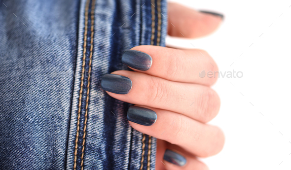 Female hand with dark blue manicured nails with jeans on white b - Stock Photo - Images
