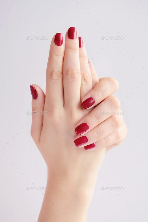 Closeup of hands of a young woman with red manicure on nails - Stock Photo - Images