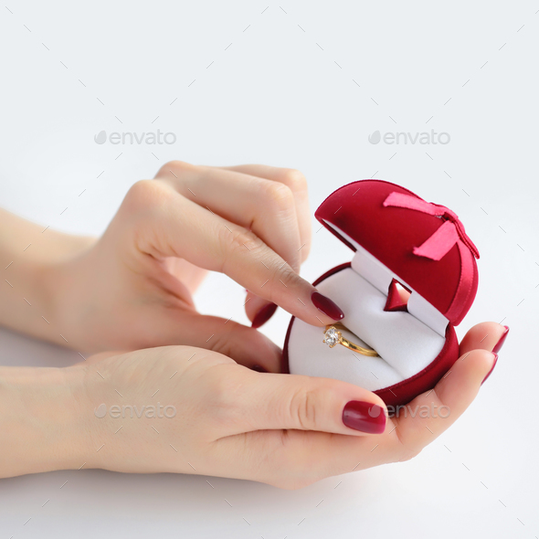 Close-up female hands holding an open red box with a wedding rin - Stock Photo - Images
