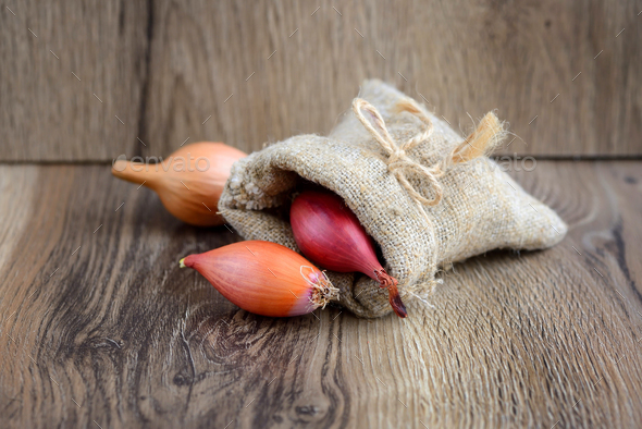 Dry bulb onions for planting in a small sack on wooden backgroun - Stock Photo - Images