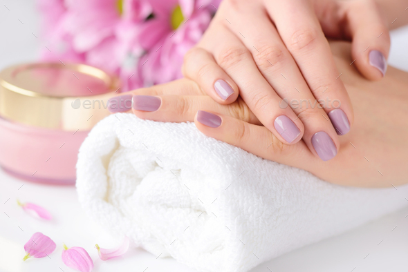 Women's hands with pink manicure are on a towel - Stock Photo - Images