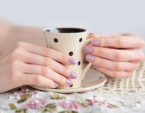 Cup of coffee in girl hands on linen tablecloth - Stock Photo - Images