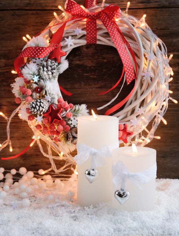 White candles on the snow with Christmas wreath and Christmas li - Stock Photo - Images