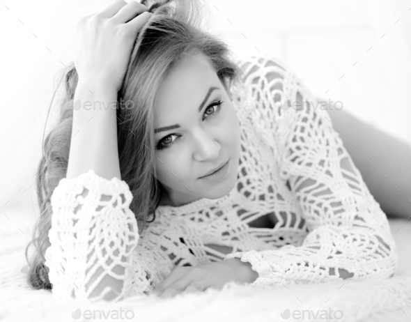 Pretty woman lying down on her bed at home. Seductive girl in wh - Stock Photo - Images