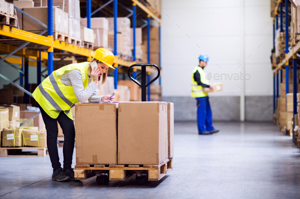 Young warehouse workers with smartphone. - Stock Photo - Images