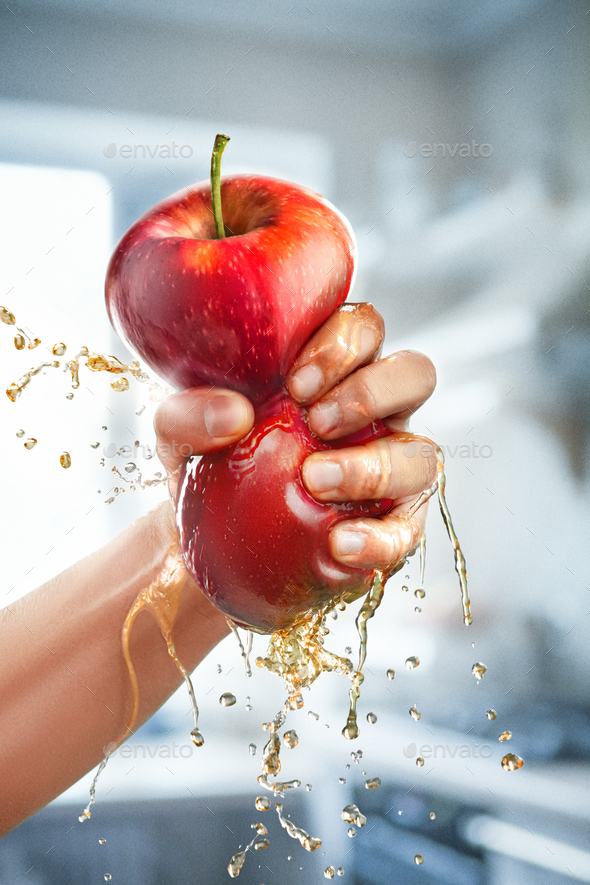 A male hand squeezes fresh juice. Pure apple juice pouring out from fruit into glass - Stock Photo - Images