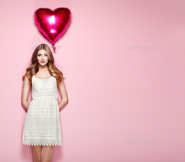 Beautiful young woman with heart shape air balloon - Stock Photo - Images
